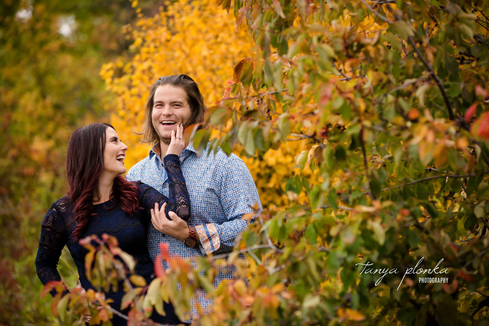 engaged couple hold each other arms while laughing