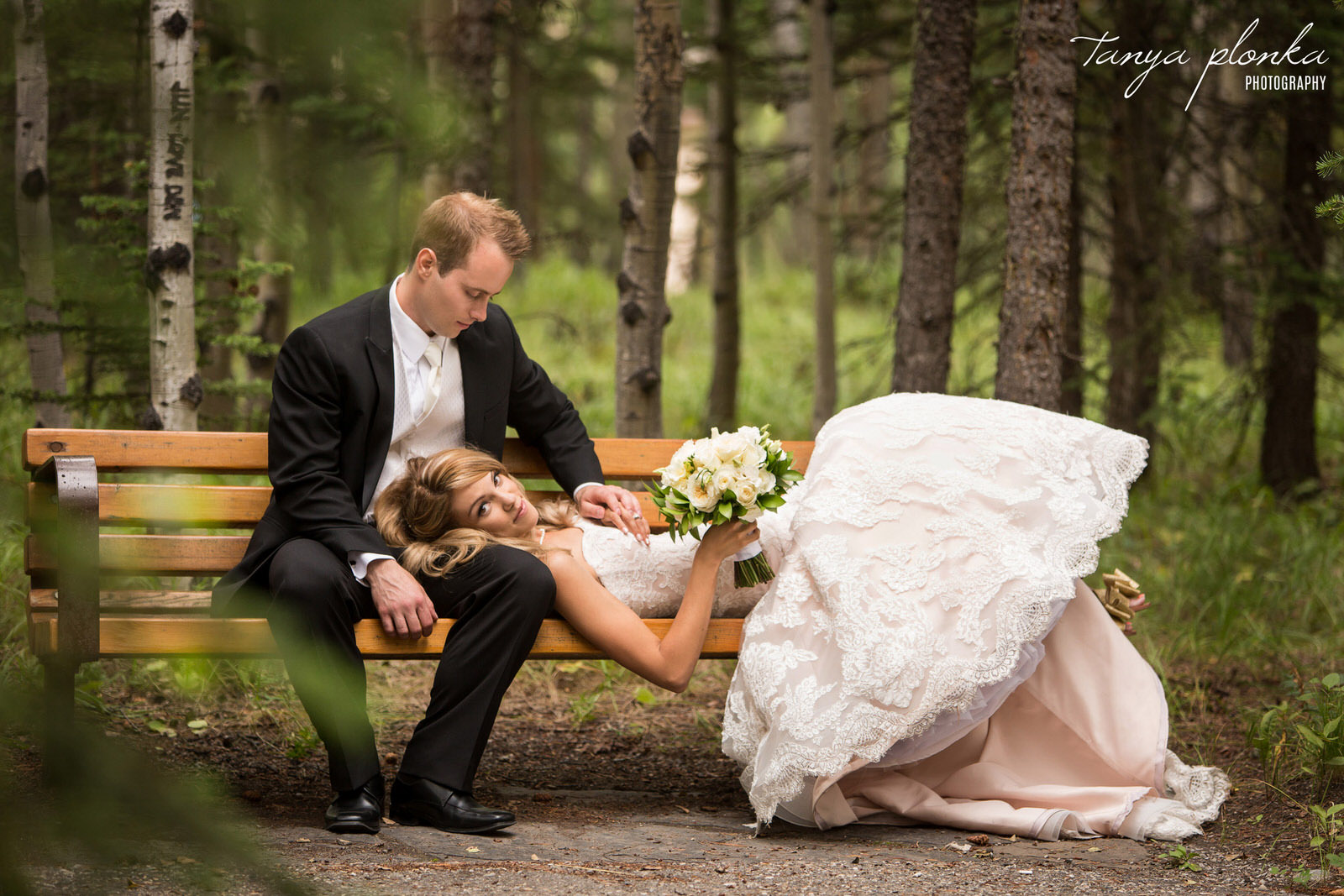 groom sits on bench at the Kananskis Delta Lodge while bride lays across his leg