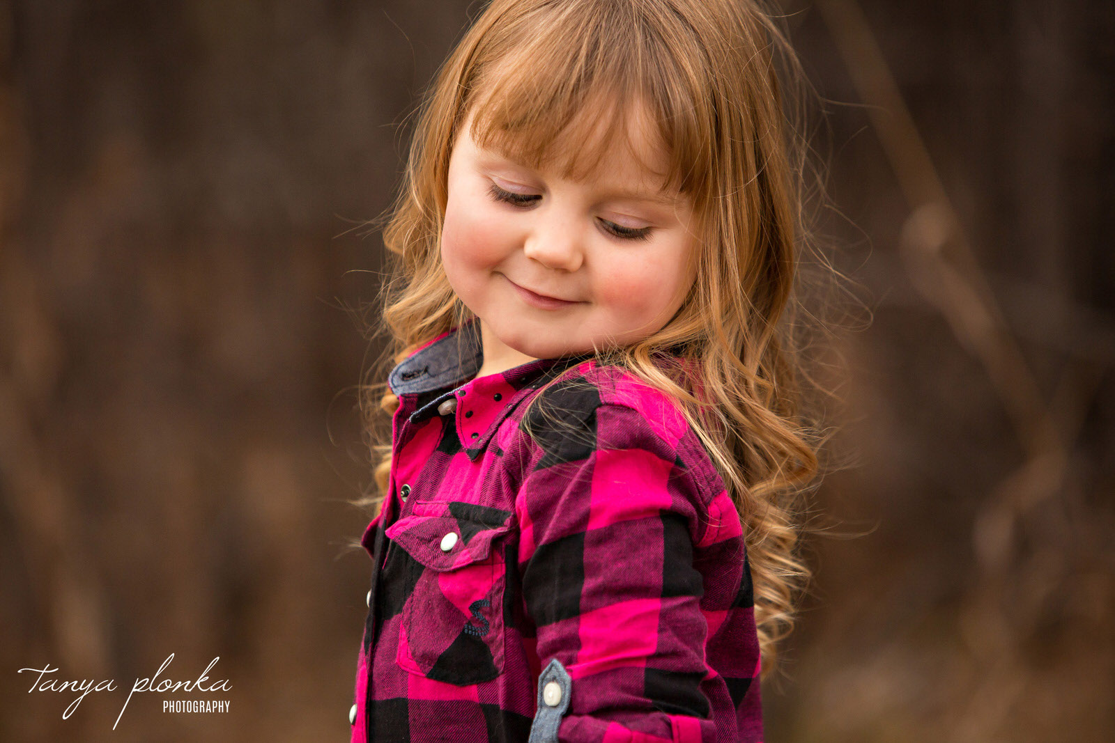 little girl wearing pink plaid shirt looks over shoulder