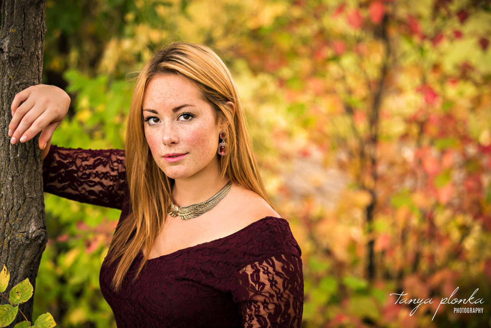 woman in maroon dress leans on tree with autumn colors in background