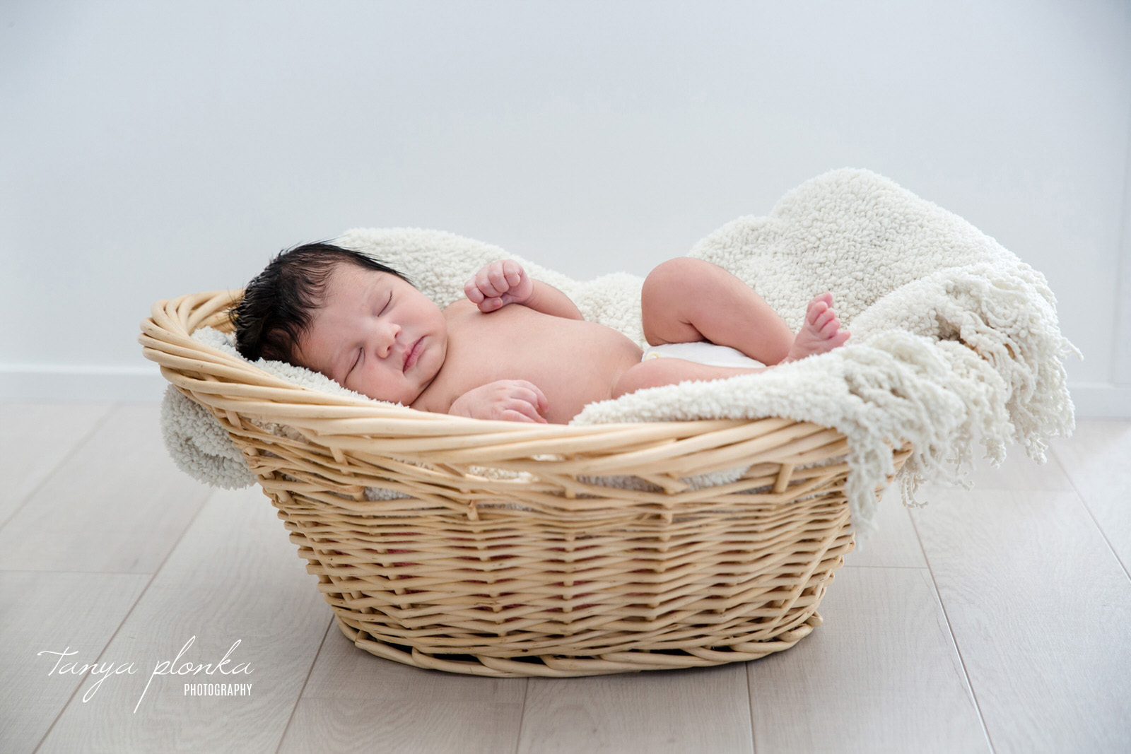 baby sleeping in wicker basket