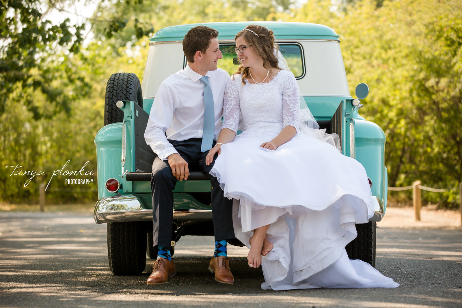 groom and bride sit together in back of vintage aqua pickup truck