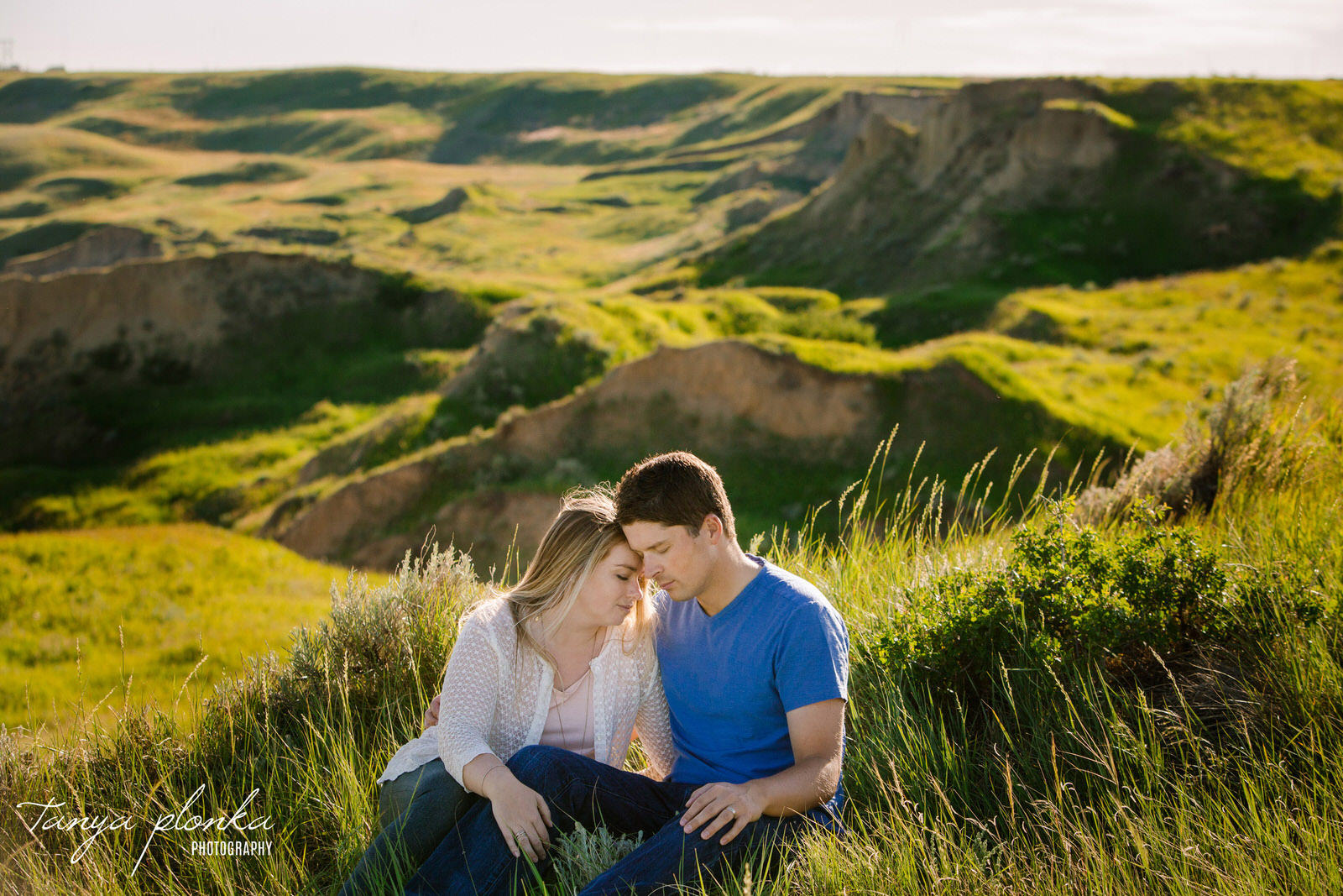 married couple sit on edge of green coulees in Lethbridge with their foreheads together