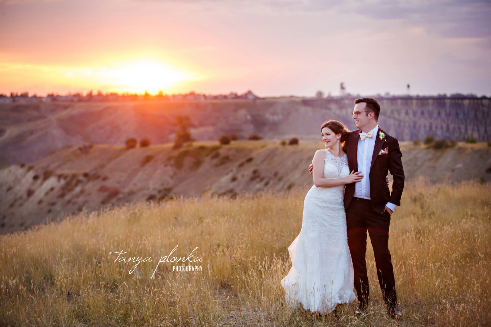 Bride and Groom stand with arms around each other in front of sun setting in coulees