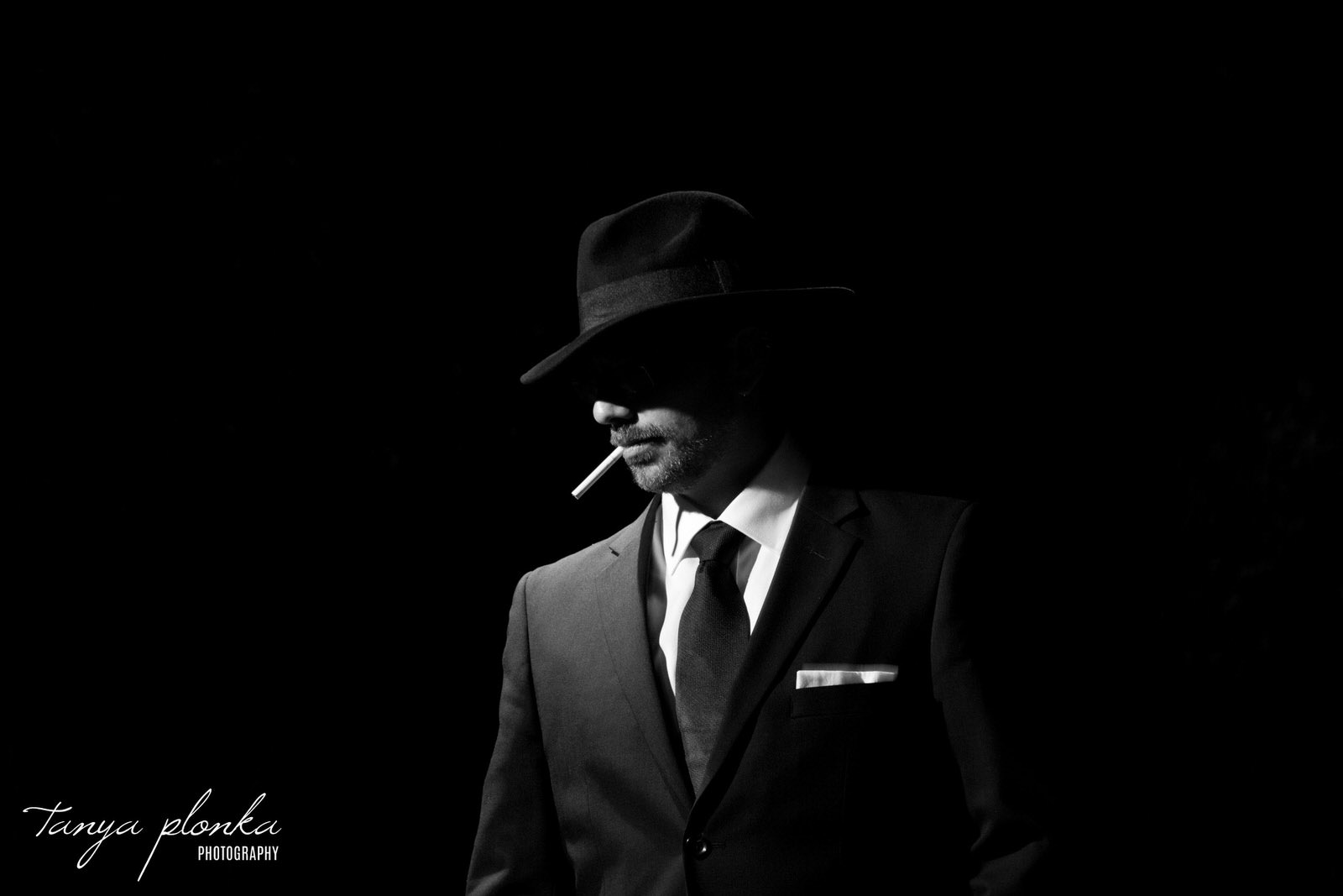 black and white film noir style photo of man with cigarette in mouth