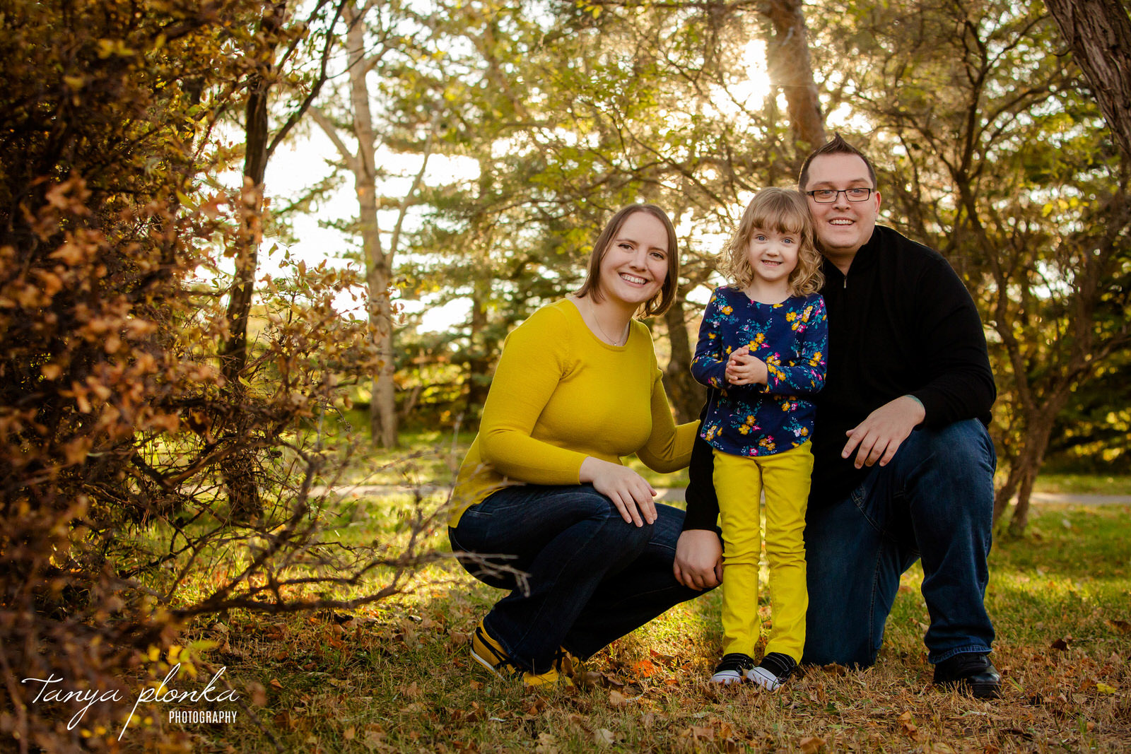 family dressed in yellow crouch on ground for photo