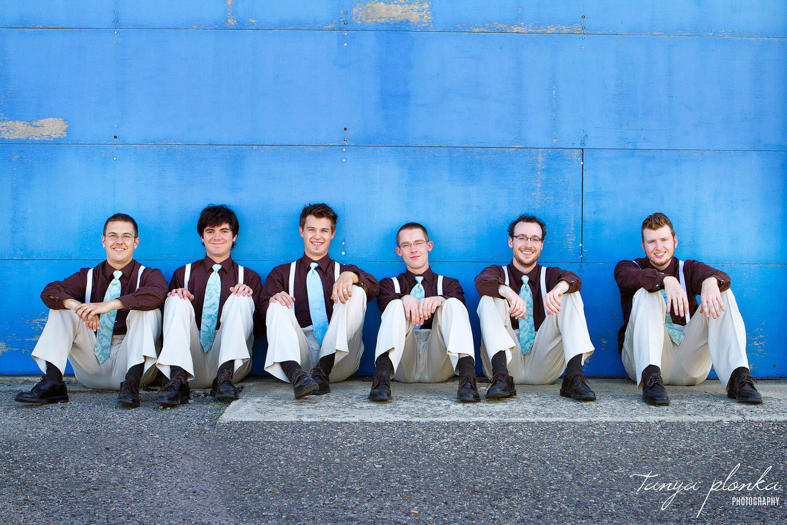 groomsmen casually sitting against blue wall in downtown Lethbridge