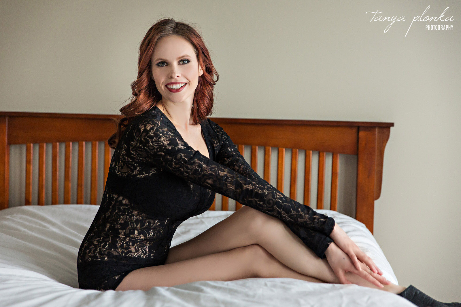 woman in black lace body suit sits on bed