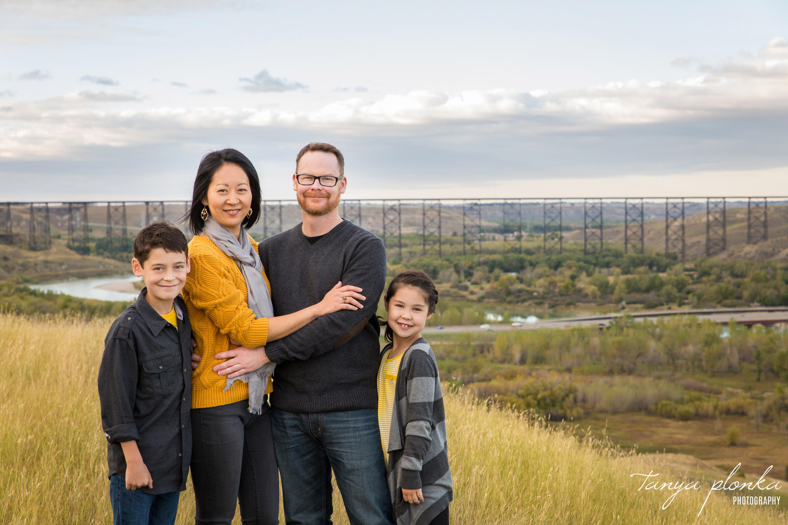family of four stand on top of coulees with high level bridge in background