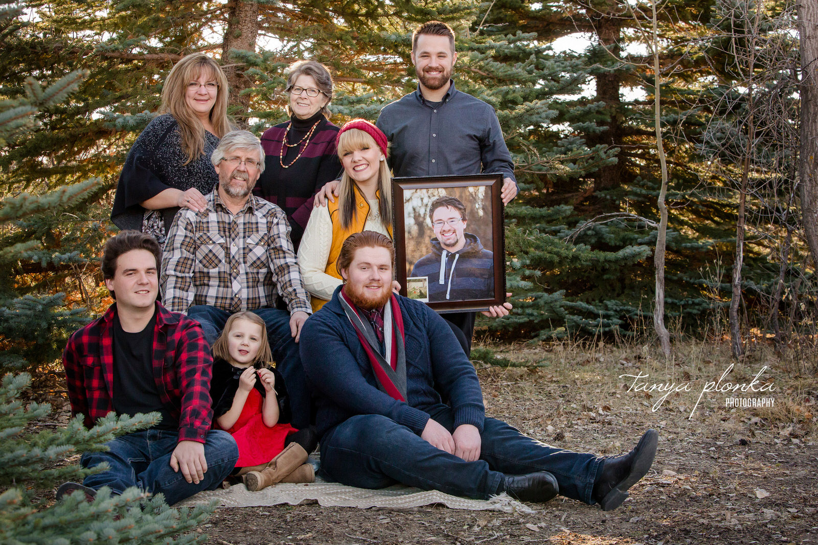 family poses in the late autumn holding photo of brother in memory