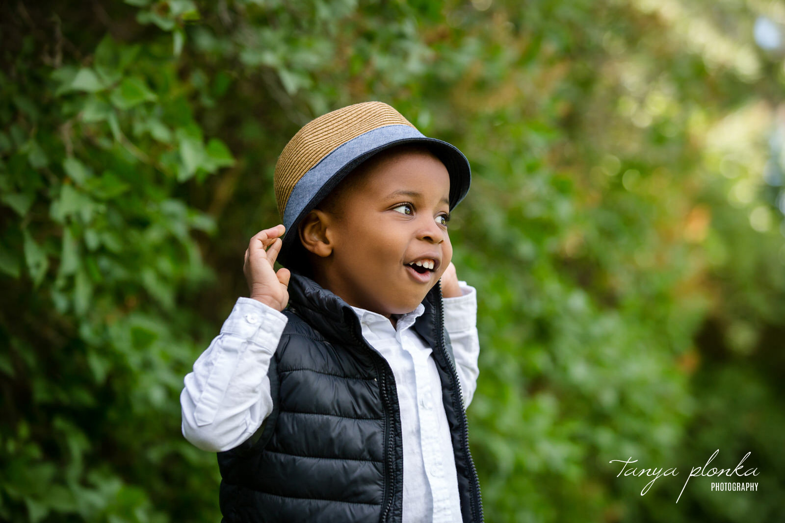 Young boy smiling while pulling on his hat