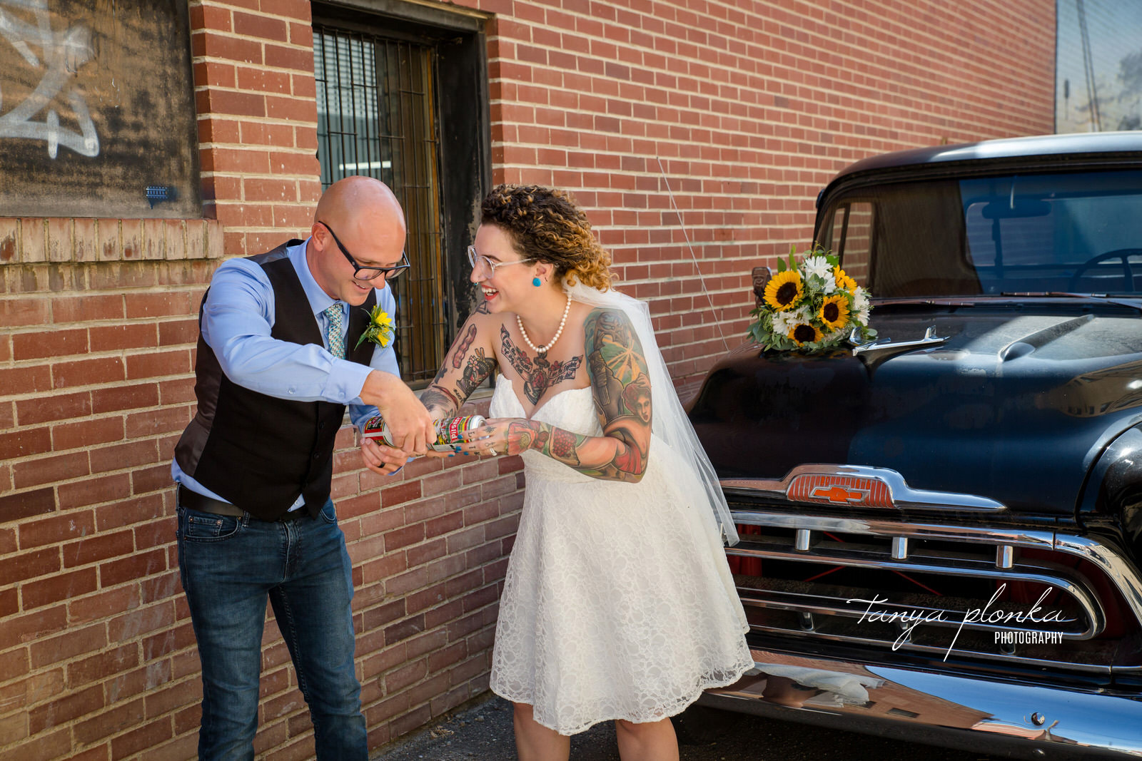 bride and groom smile at each other while holding cans of Pilsner