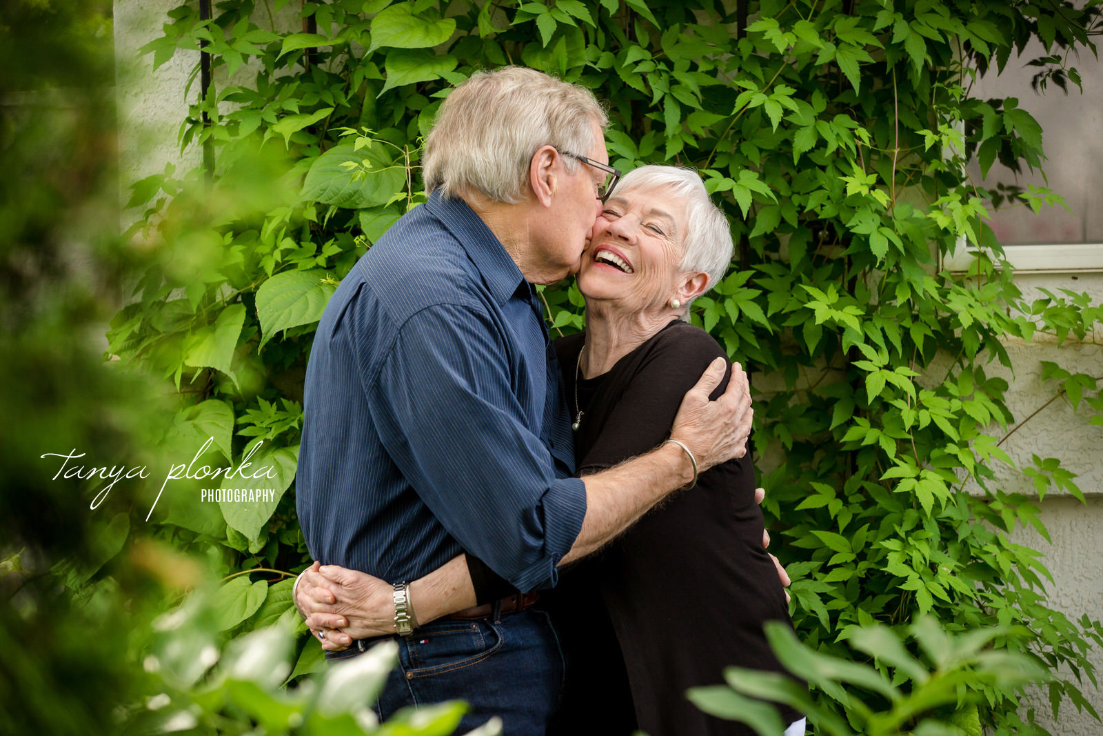 married senior couple with husband kissing wife on cheek while she smiles