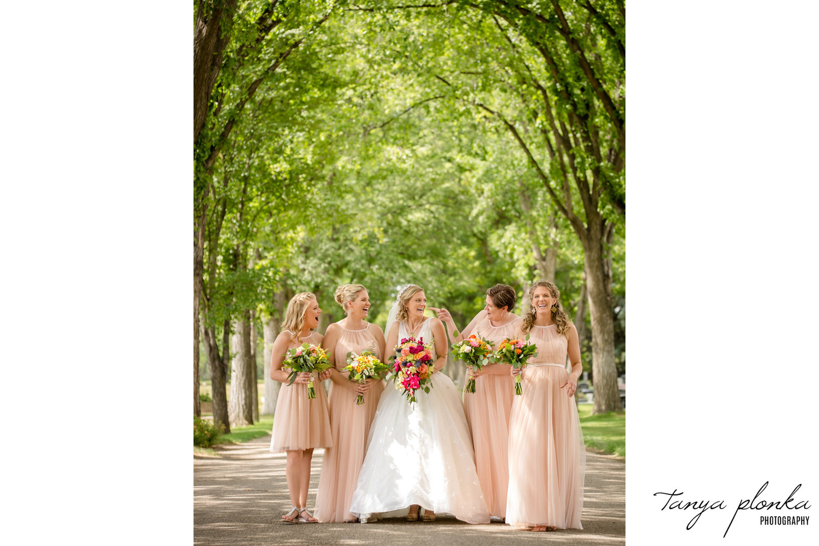 Bride and bridesmaids in light pink dresses stand in tree lined street laughing
