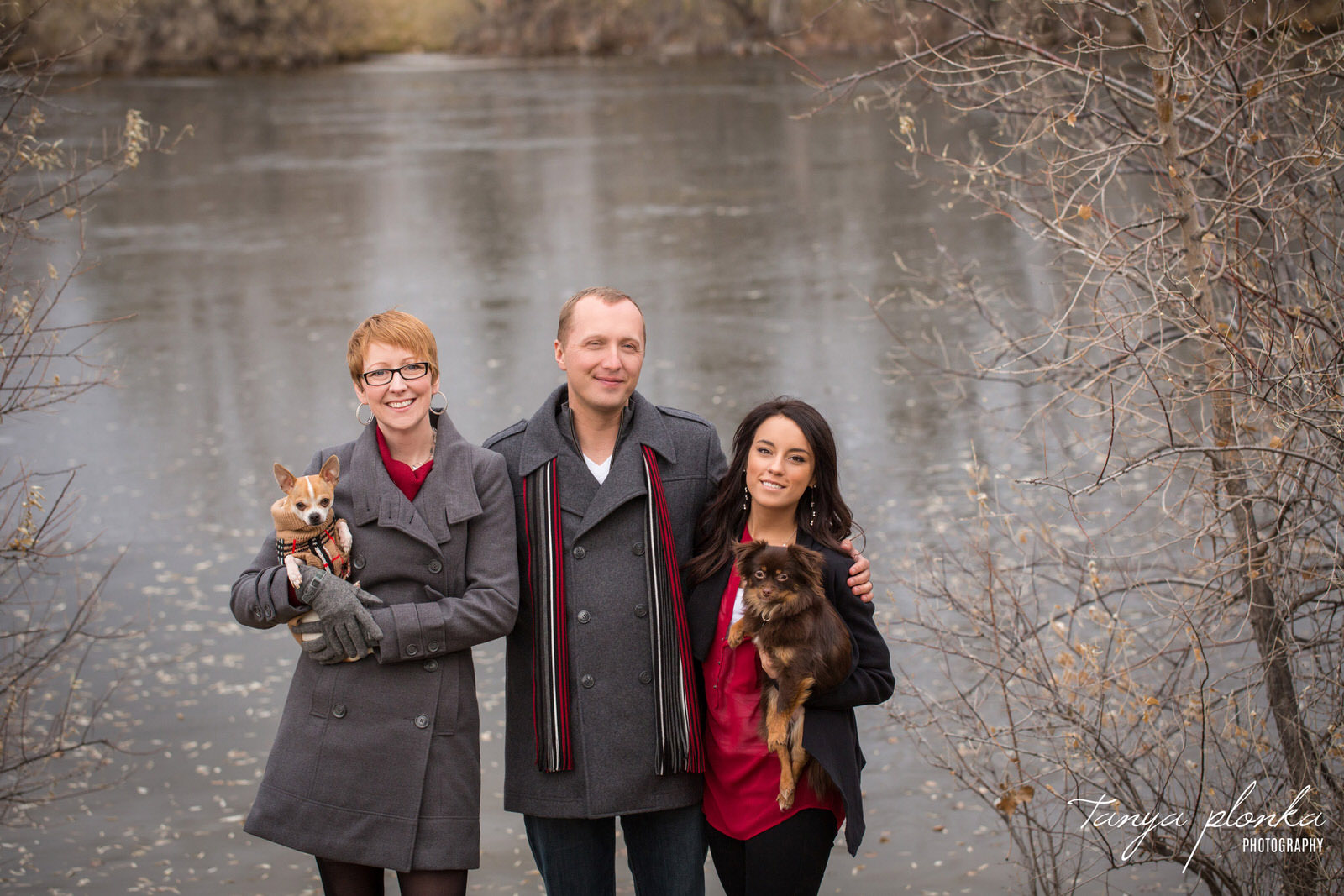 adult family of three holding small dogs stand in front of frozen lake