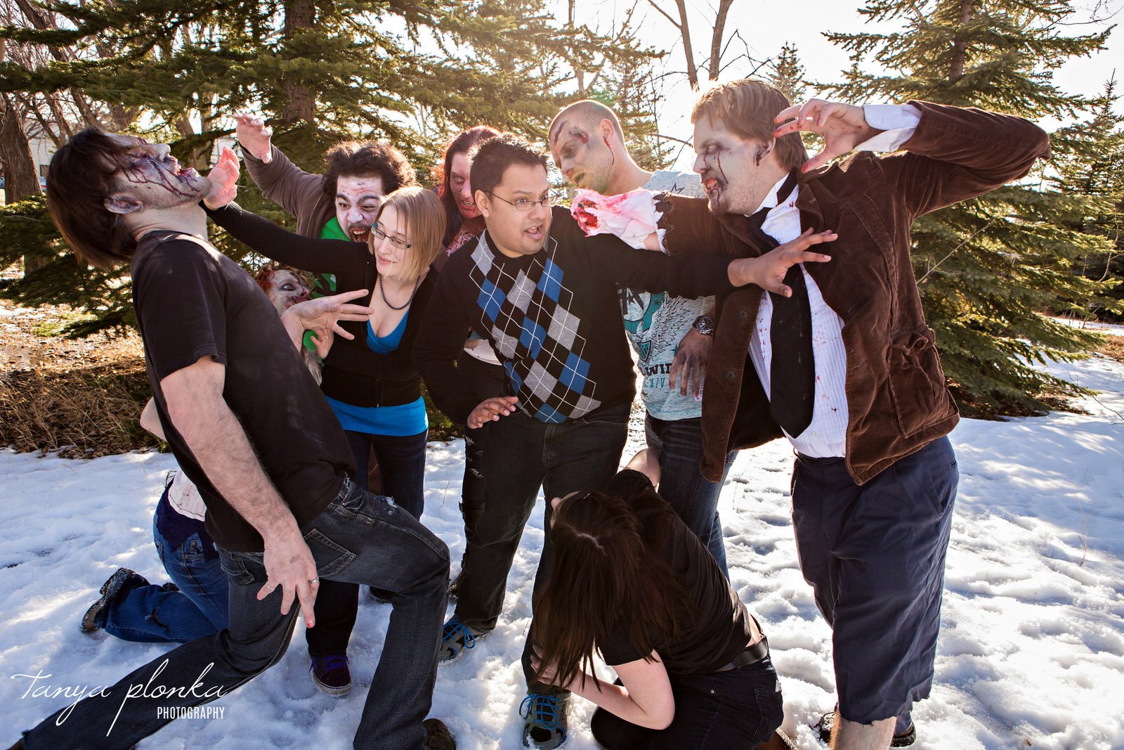 pack of zombies attacking a couple in the snow