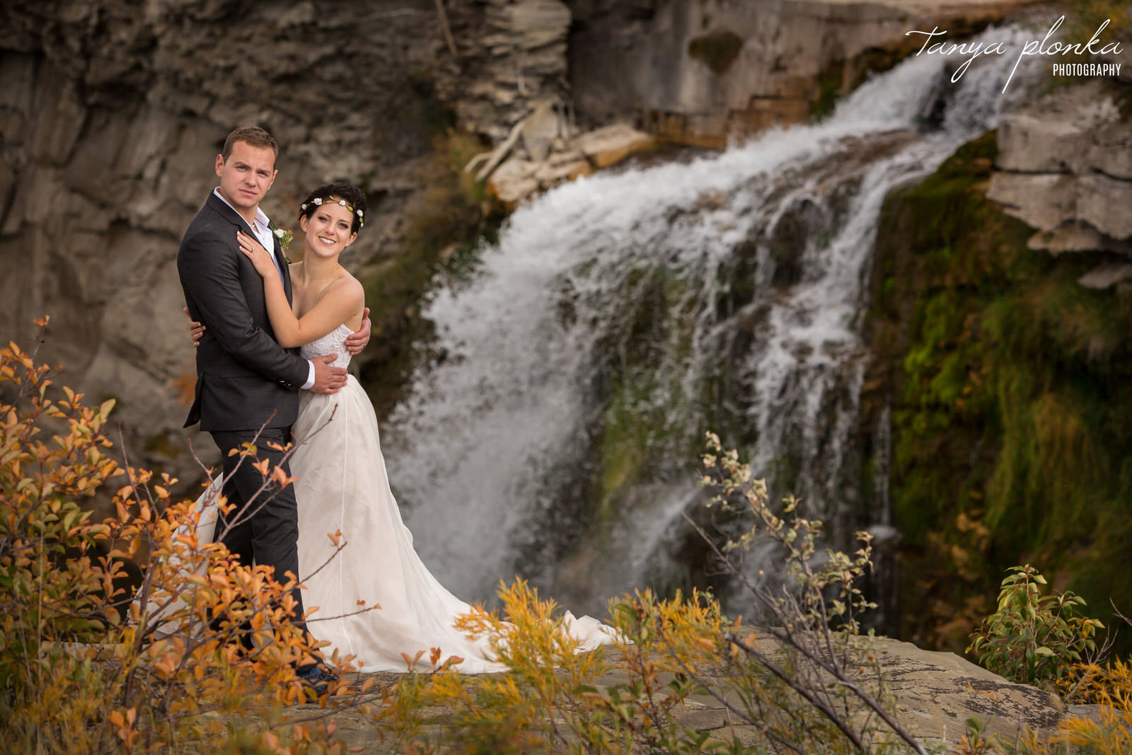 wedding couple embrace on cliff in front of Lundbreck Falls