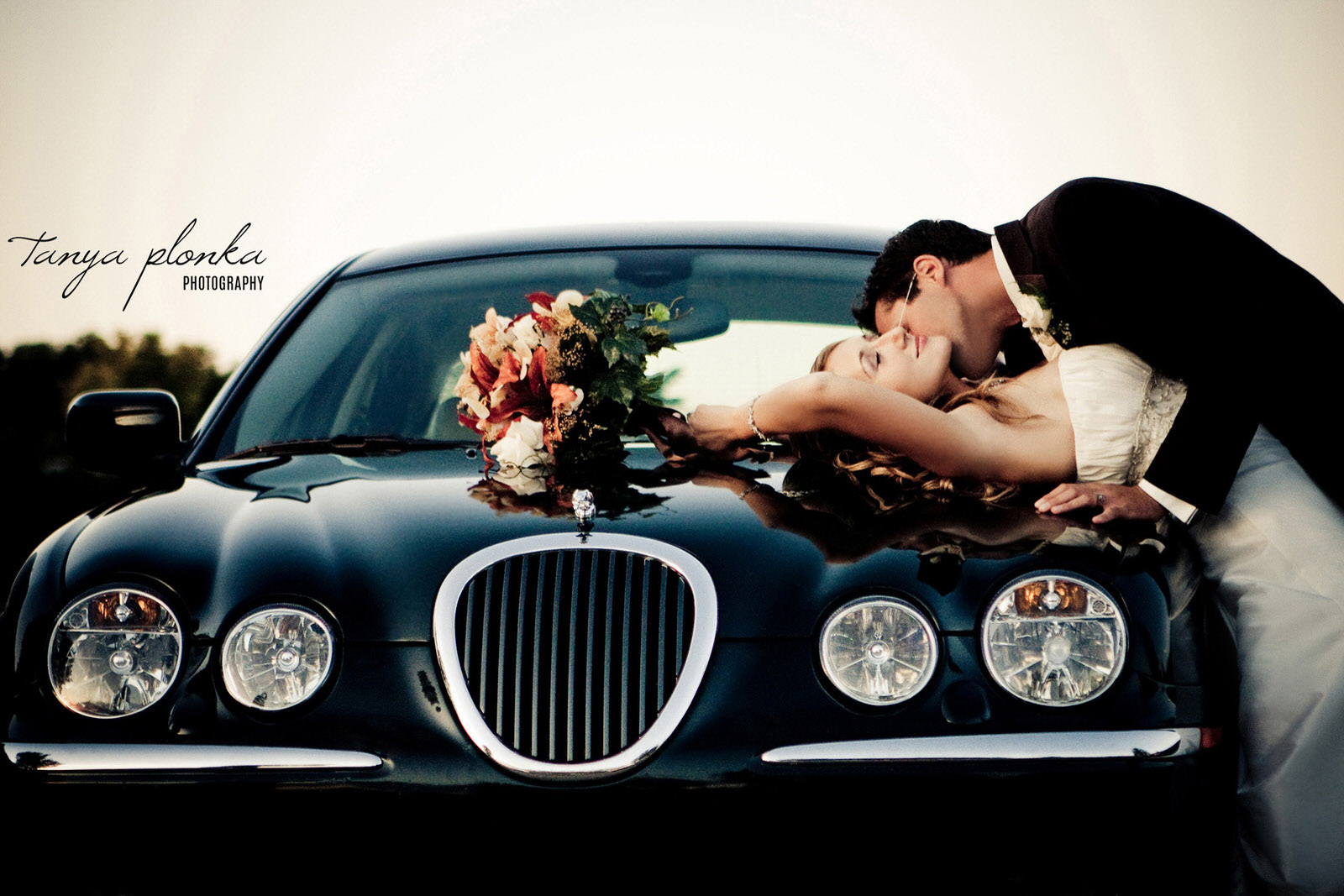 wedding couple kissing on black Jaguar car in Medicine Hat