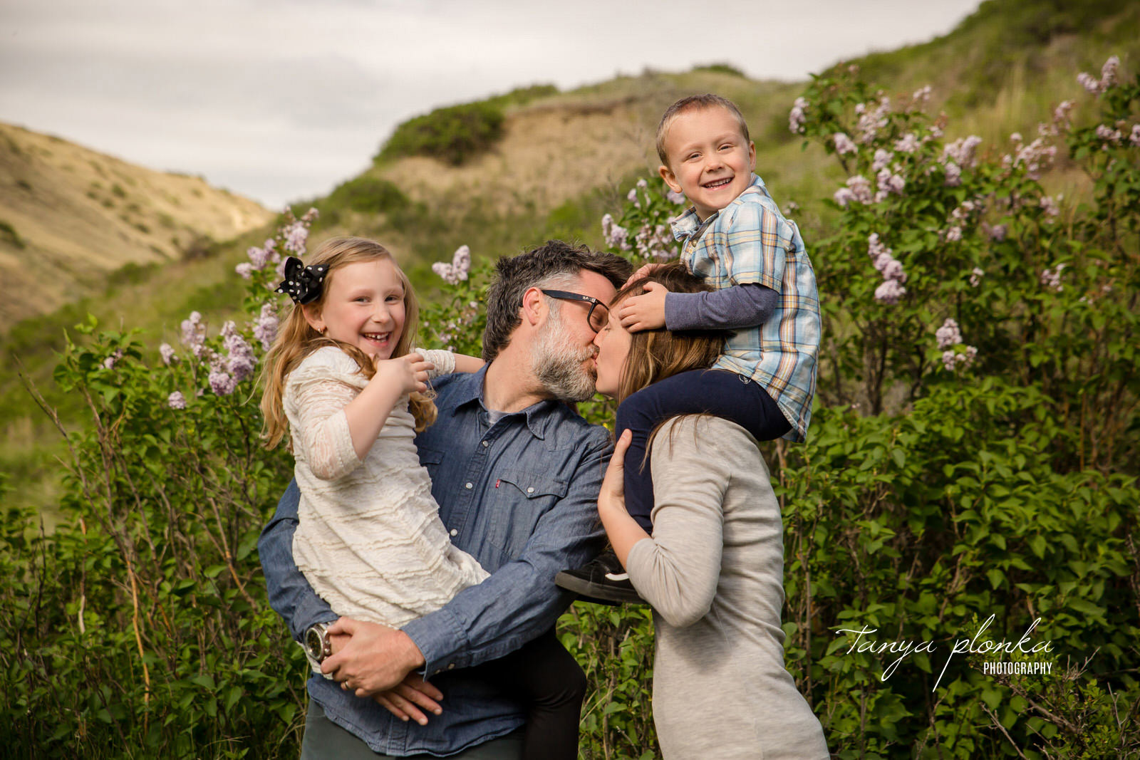 Mom and Dad kiss in front of lilacs while their children giggle
