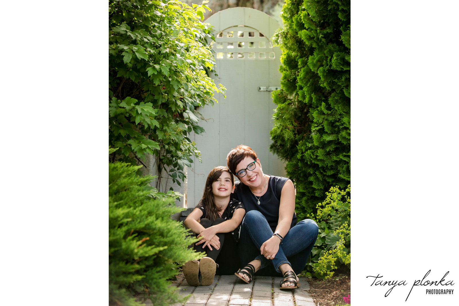 mother and daughter sit on sidewalk in front of gate in backyard