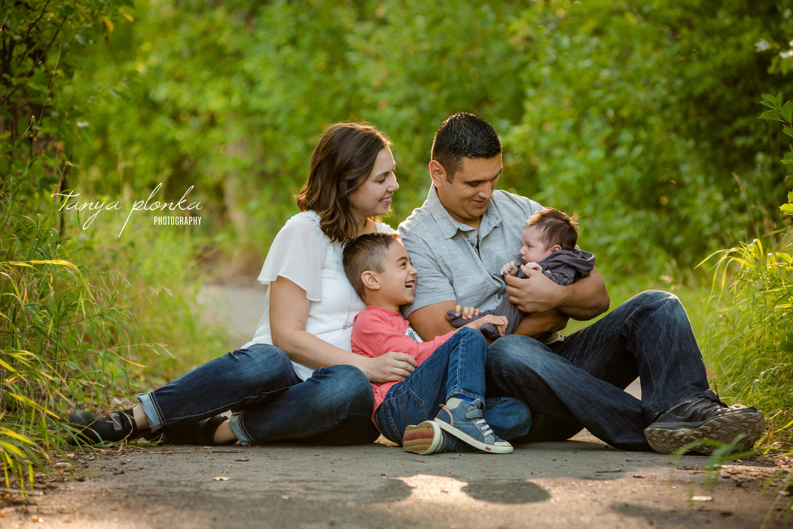 family sits on nature path and smiles at newborn baby