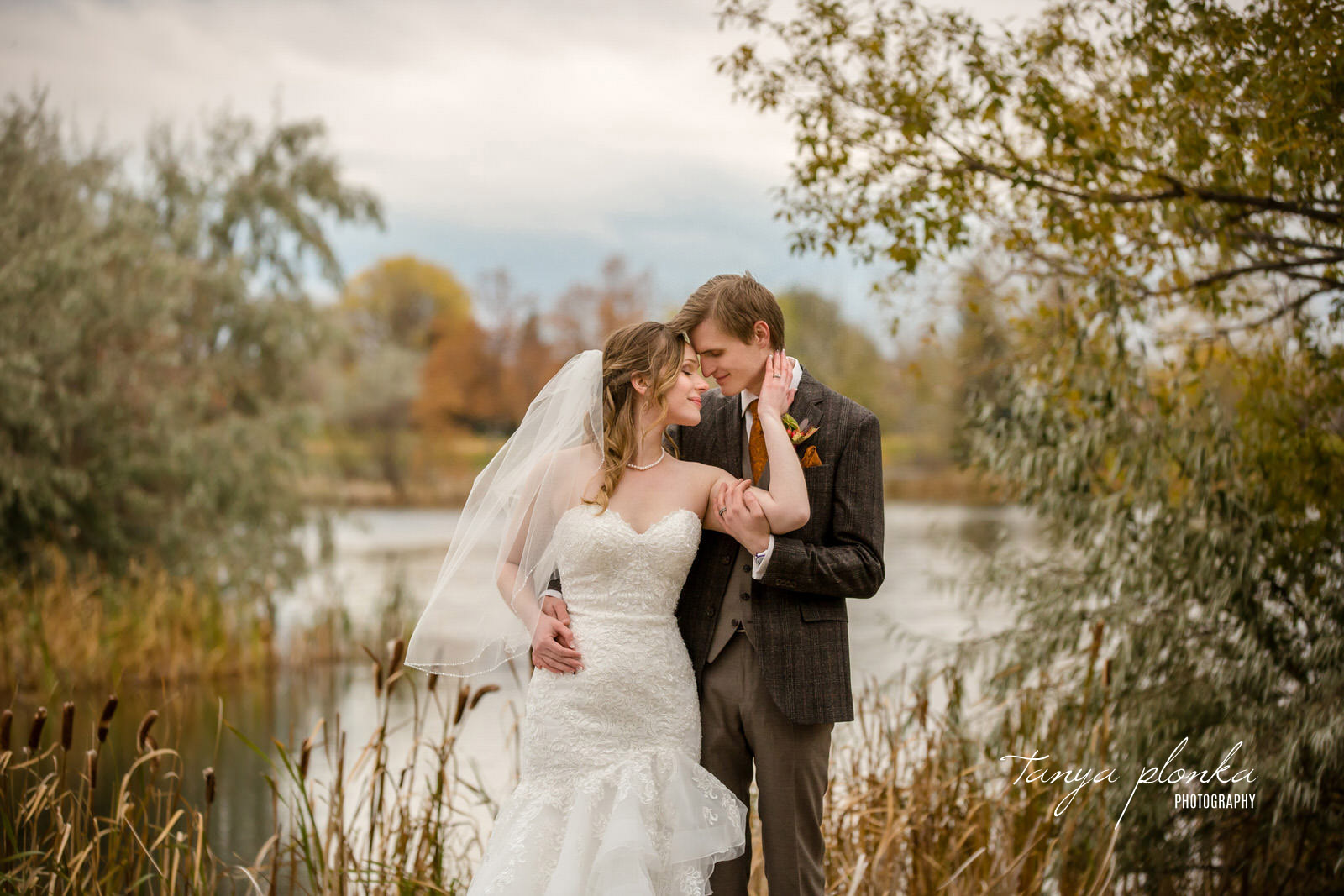 bride and groom embrace with eyes closed standing in front of autumn scene with Nicholas Sheran Lake out of focus in background