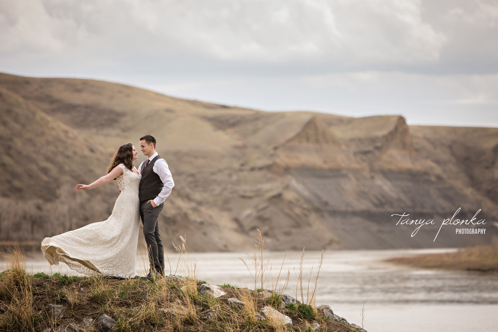 bride and groom standing in foreground of coulees