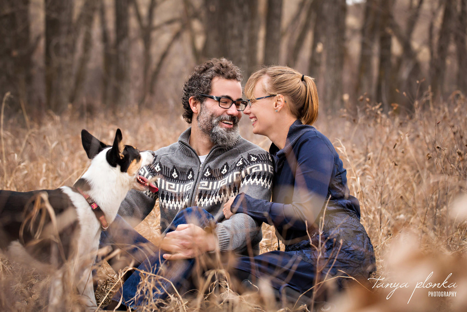 couple snuggle in long autumn grass while dog looks at them