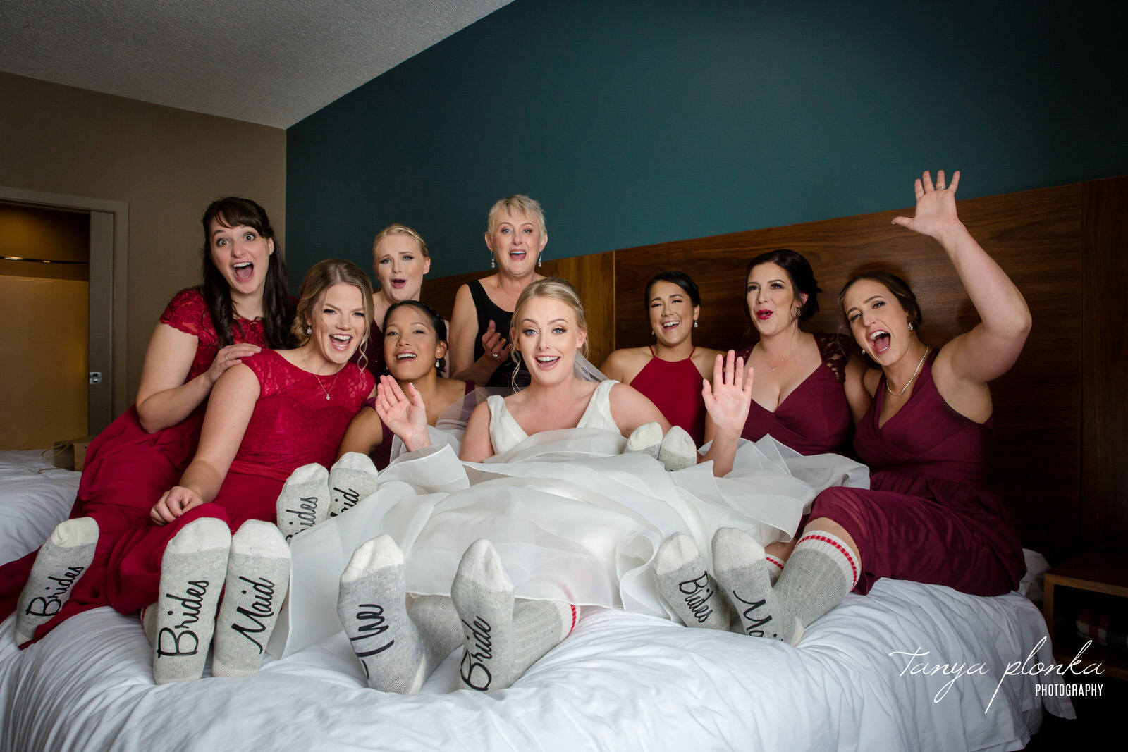 bride and bridesmaids with custom matching socks sit together on bed cheering