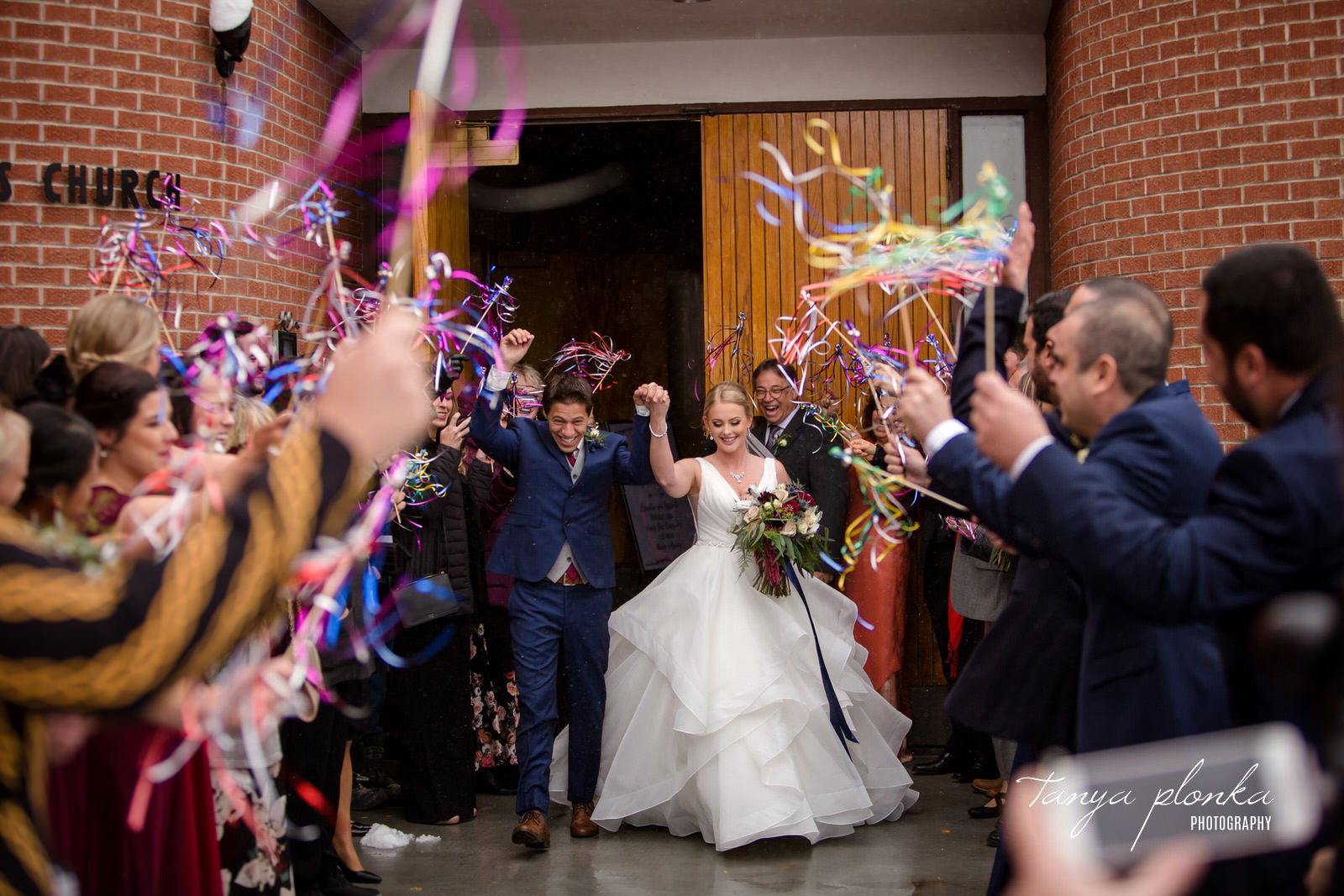 groom and bride exit church while guests wave streamers