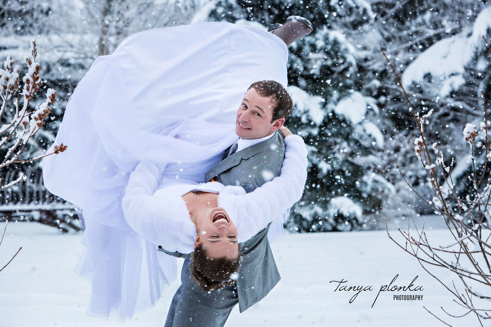 groom picks up and dips laughing bride in a snow storm