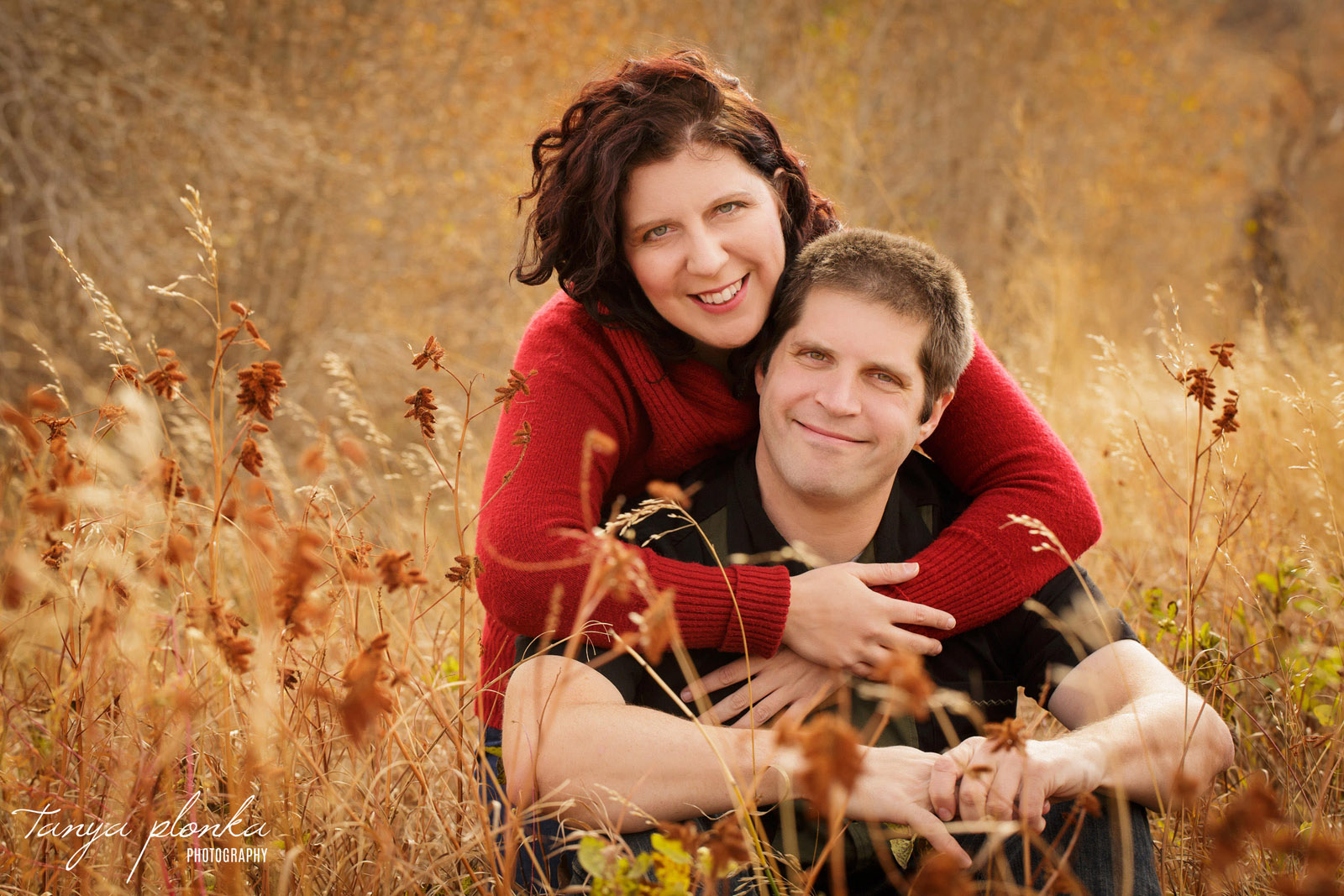 couple sitting in long golden autumn grass in Popson Park