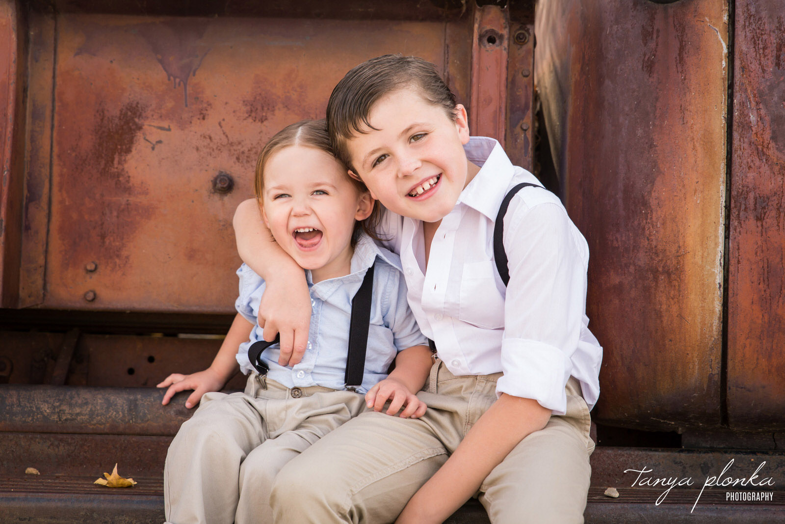 two young brothers wearing suspenders sitting on edge of rustic vintage truck