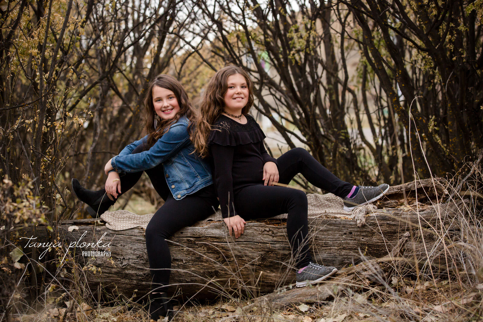 two sisters sit back to back on a log