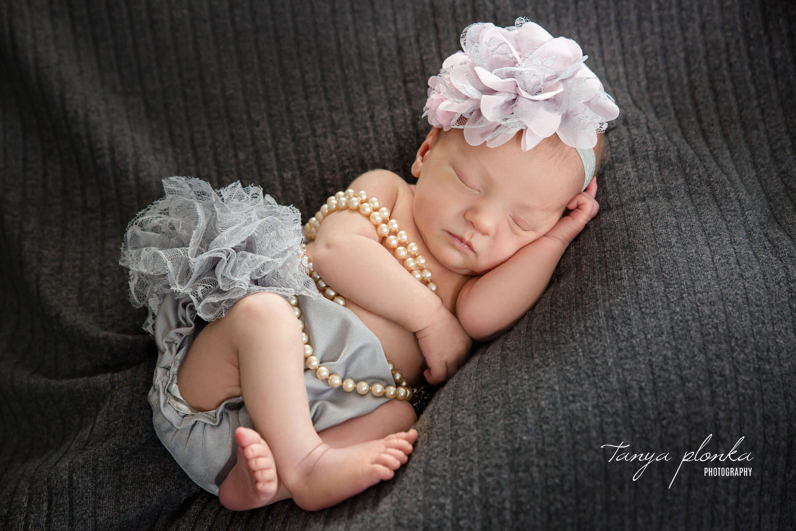 Sleeping baby wrapped in pearls