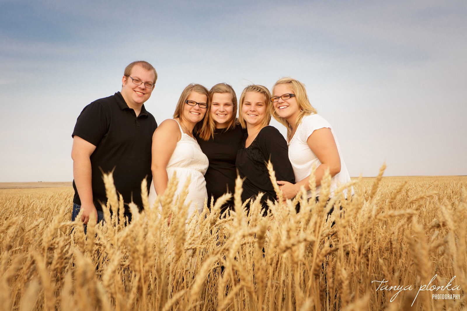 five siblings standing in wheat field