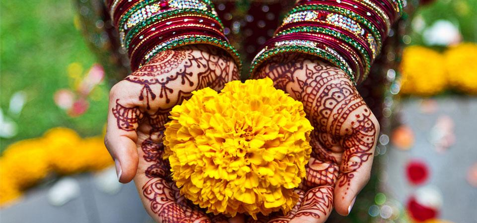 Bride holding flower in hands covered in henna