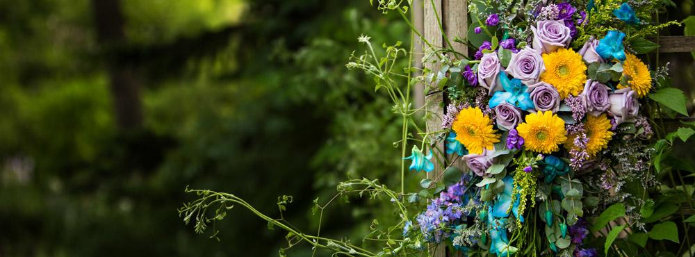 bridal bouquet made of yellow, purple, and blue flowers against a green backdrop
