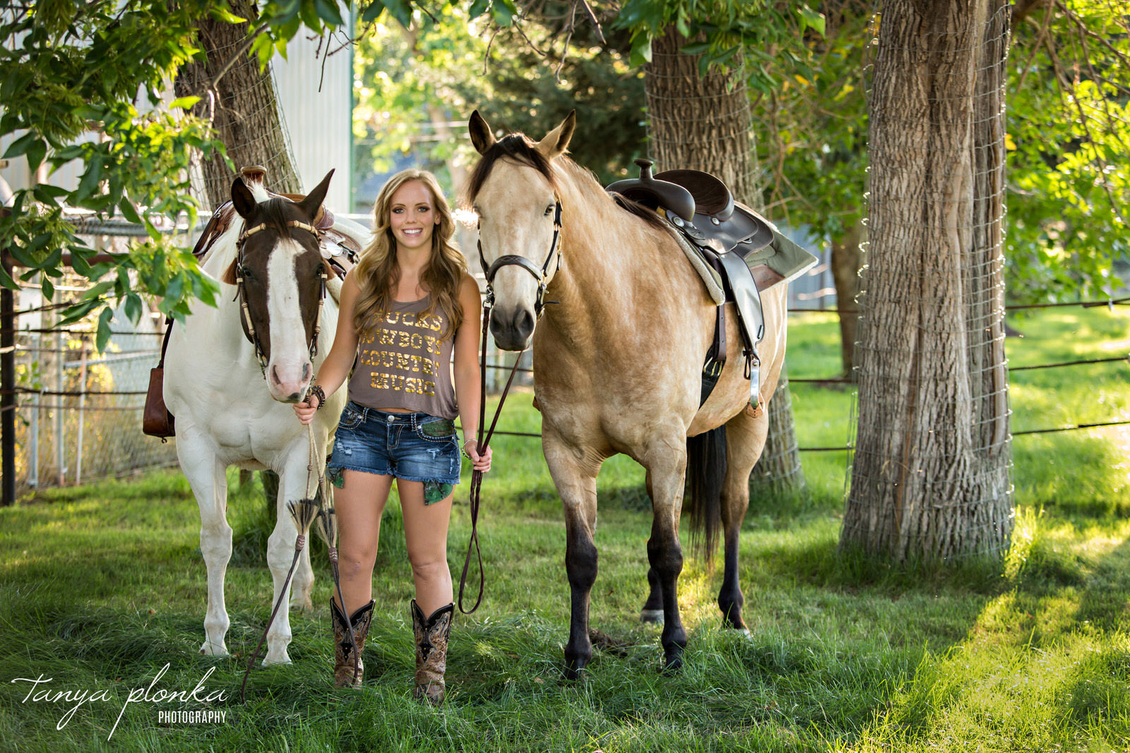 blonde woman stands between two horses while holding reigns in Taber