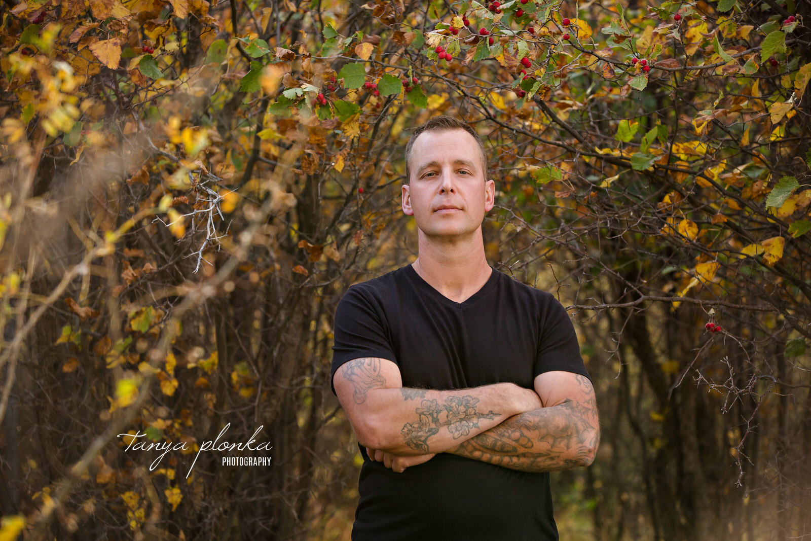 Tattooed man with arms crossed in autumn
