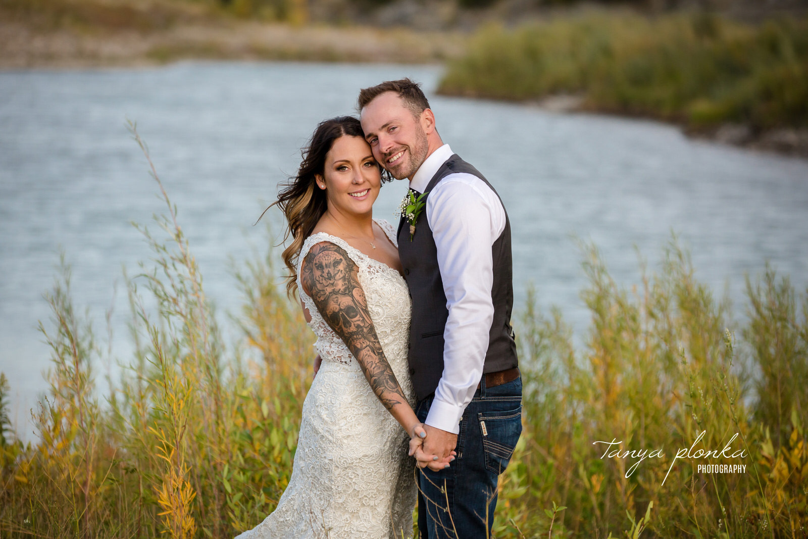 wedding couple with tattooes smiles at camera while holding hands