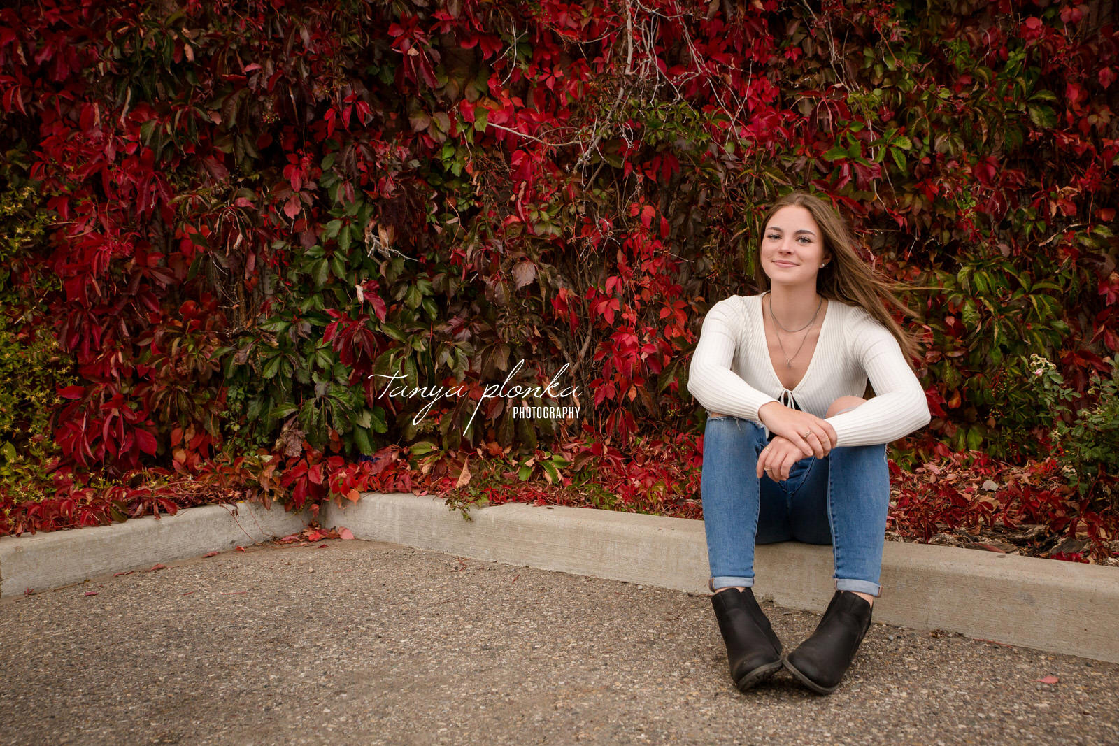 Teenager sitting in front of red leaves