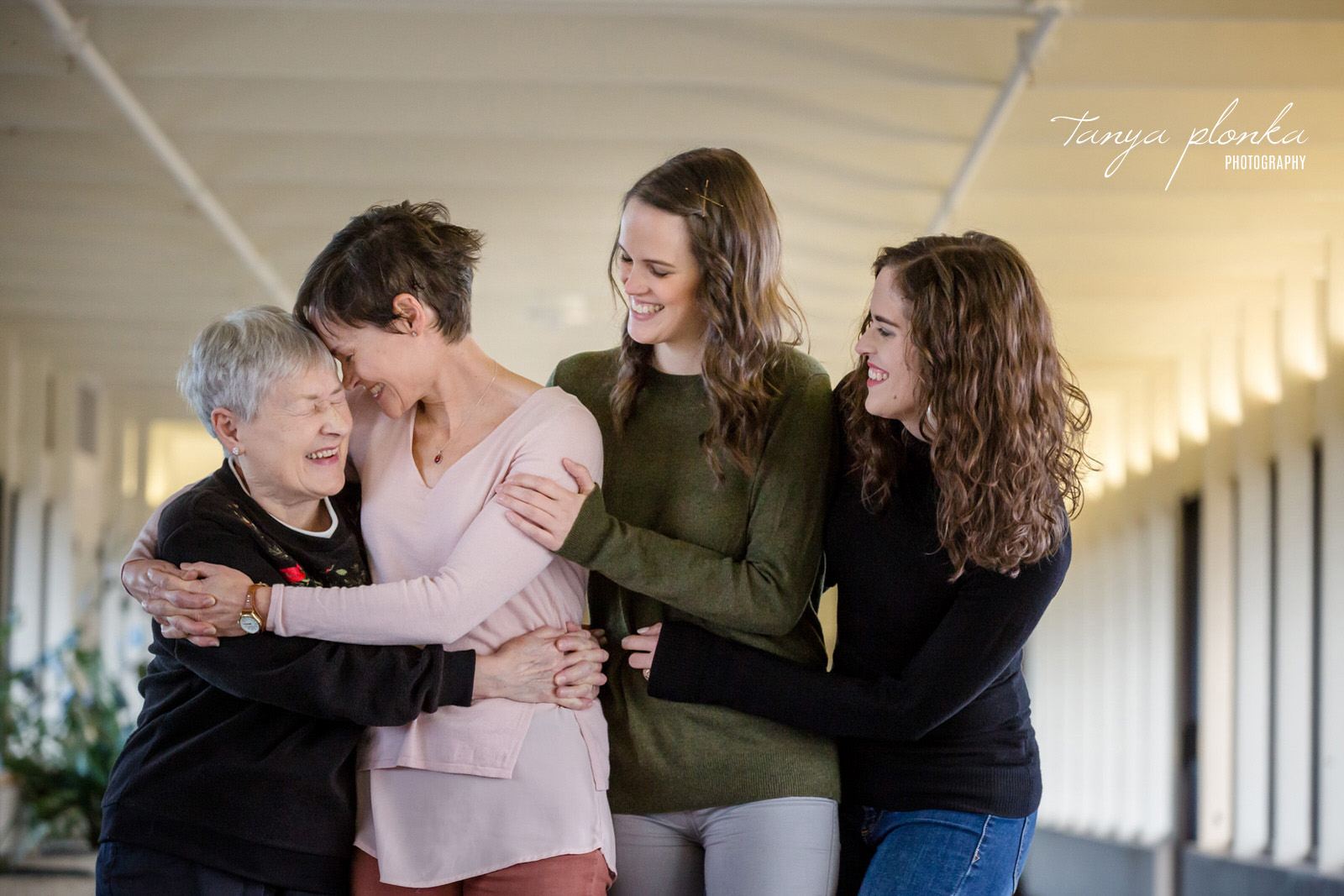 Grandma, mother, and daugthers stand in a row hugging while mother puts forehead to grandmother