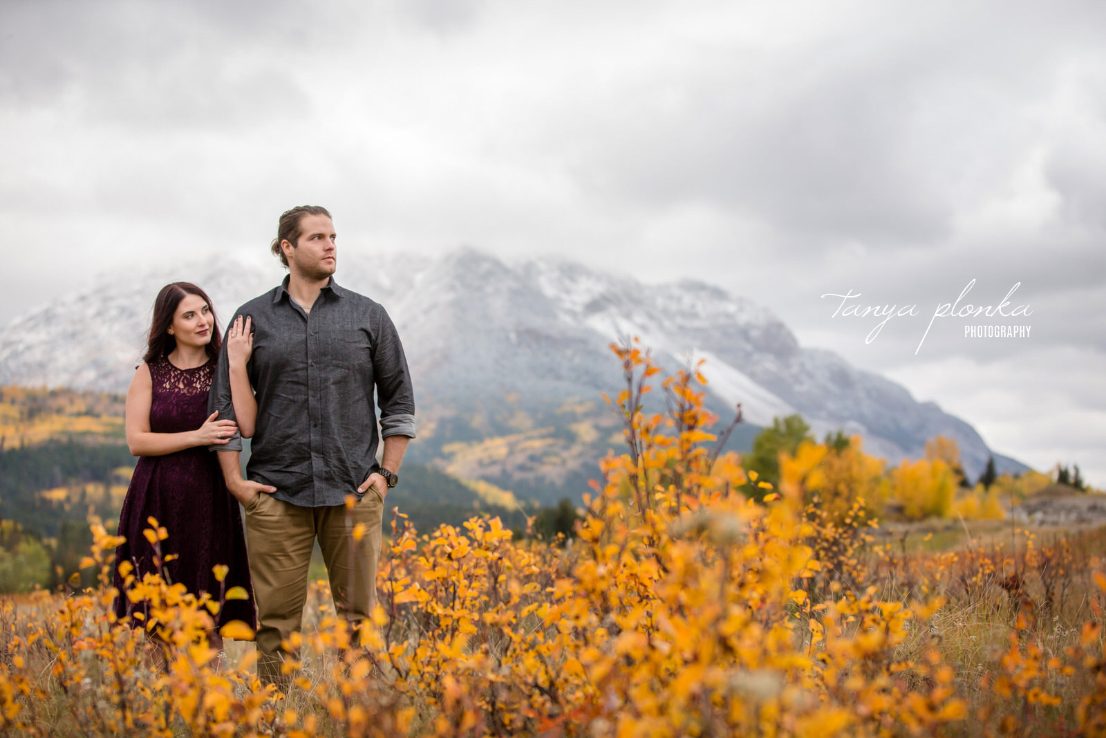 Couple are standing and looking to the right in front of Turtle Mountain in the autumn