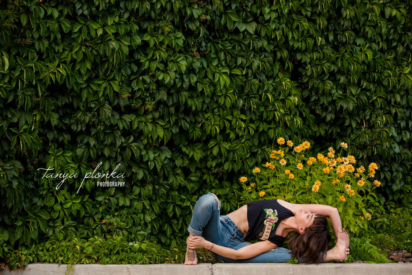woman doing yoga pose in urban setting with yellow flowers behind her