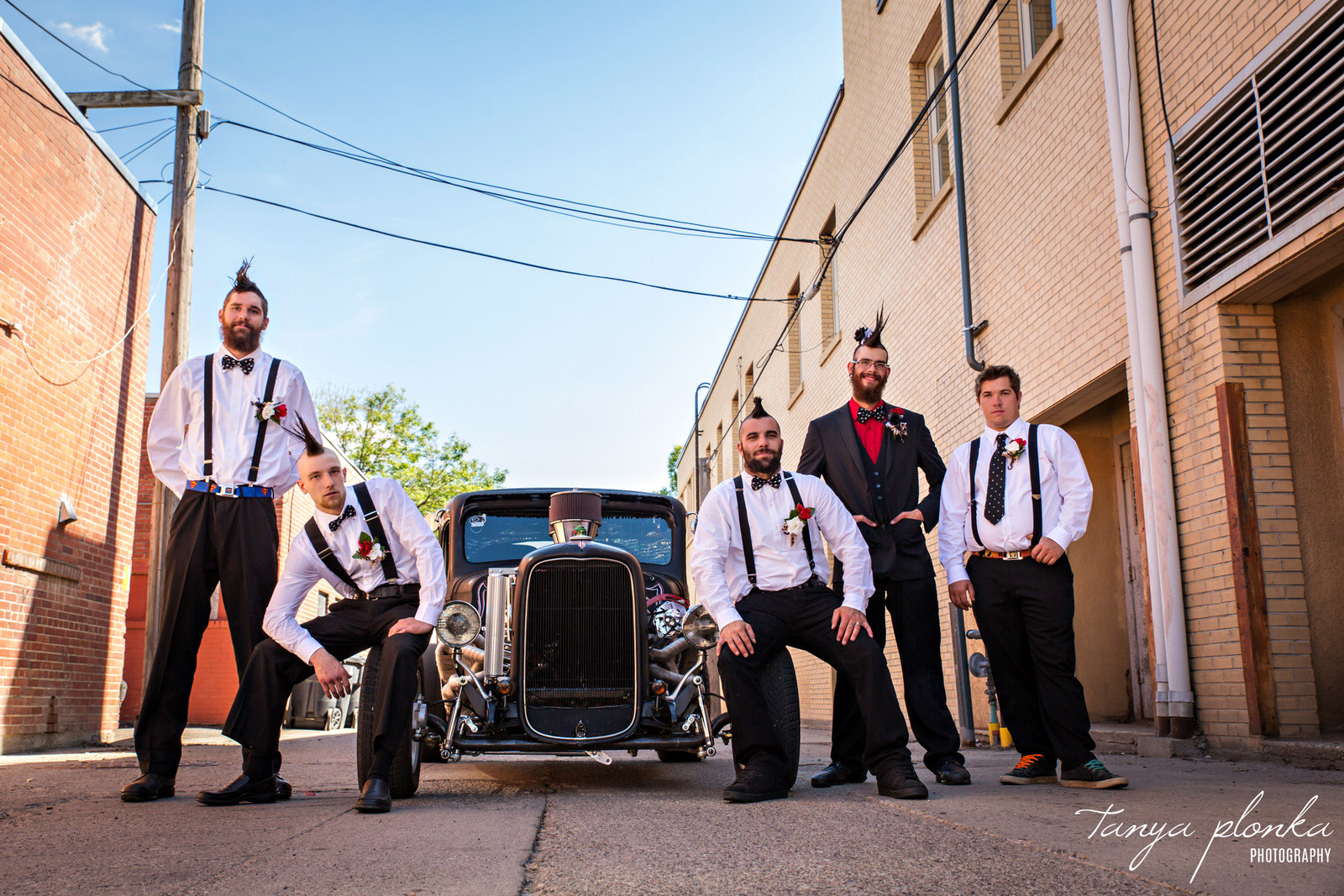 groomsmen with mohawks sit around around vintage car in alley in downtown Lethbridge