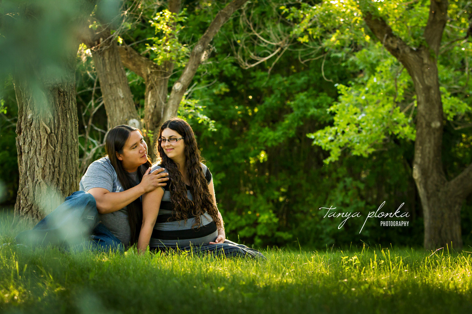 expecting couple looking at each other sitting in grass in forest