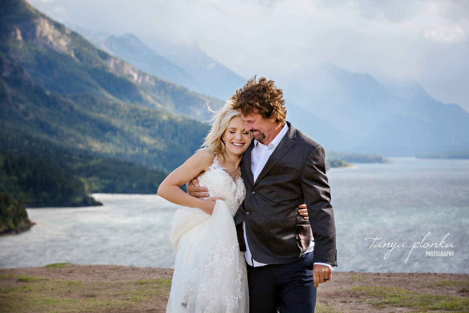 Couple embrace on the cliff behind the Prince of Wales Hotel while being windswept