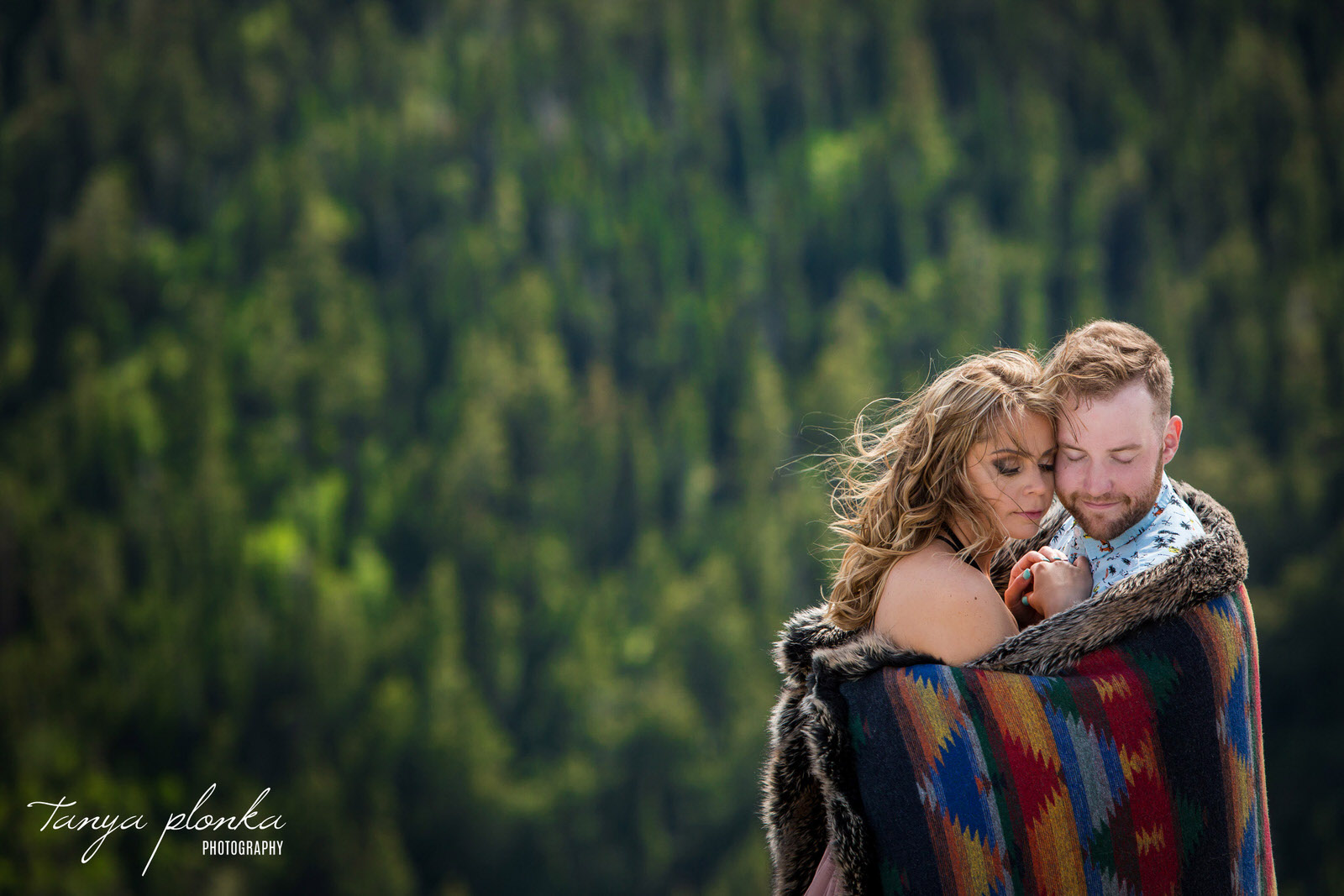 couple embrace wrapped in blanket overlooking a forest mountain scene in Waterton