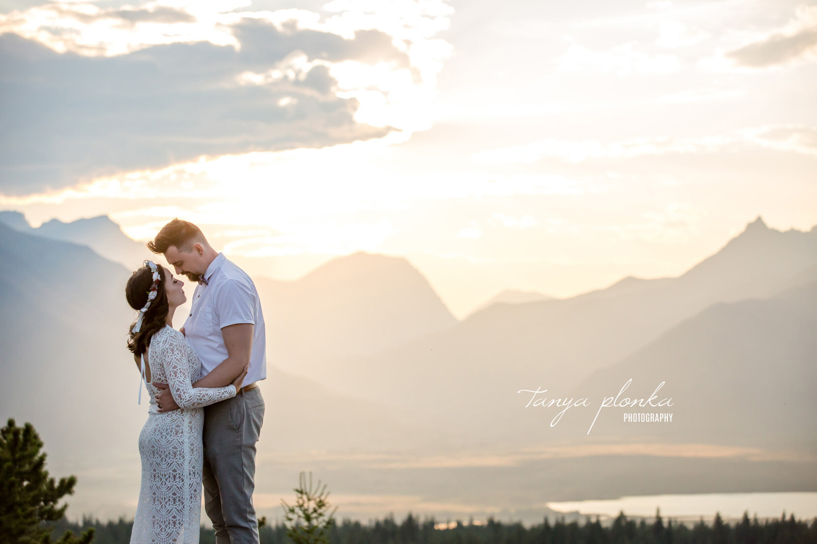 Couple embrace at sunset with mountains in the background